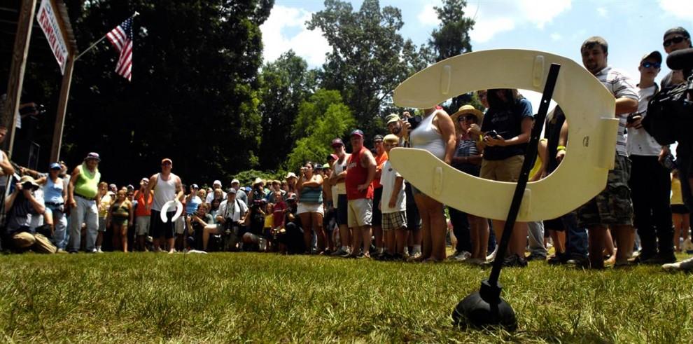 Один из участников соревнований метает «южную подкову» (сидение от унитаза). (Stephen Morton / Getty Images)