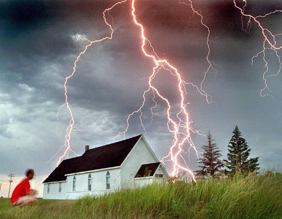 4) Нил Фрейзер наблюдает за тем, как молния бьет за зданием церкови в городе Россера, штат Манитоба. Снимок сделан рано утром 30 июля 1995 года. (Marc Gallant/AP)