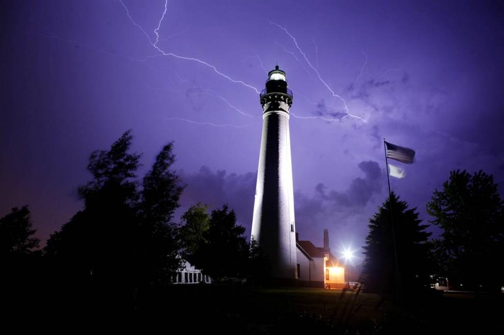 14) Вспышки молний над маяком Винд Пойт на озере Мичиган во время сильной грозы. Снимок сделан 18 августа 2005 года. (Darren Hauck/Getty Images)