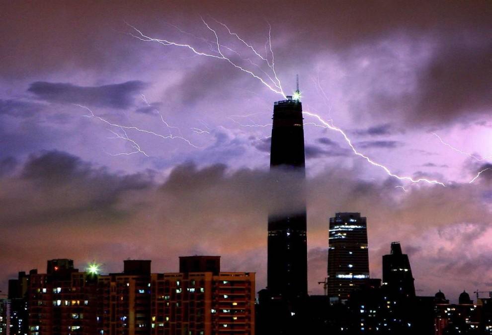 12) Молния бьет над вершиной международного финансового центра в китайском городе Гуанчжоу в провинции Гуандонг. Снимок сделан 3 июня 2009 года. (AP)