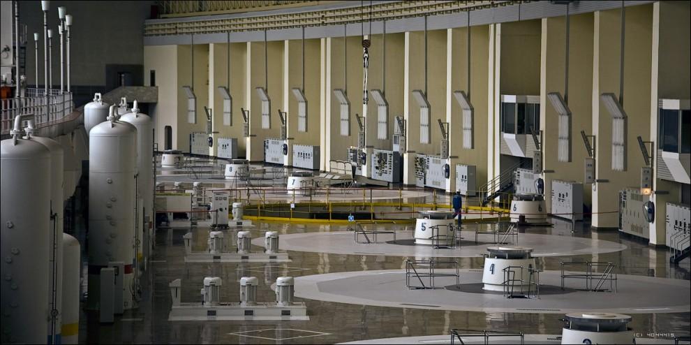 24) Десять гидротурбин Саяно-Шушенской ГЭС явились новым этапом в отечественном гидроэнергостроении. Каждая турбина РО-230/833-В-677, снабженная рабочим колесом из нержавеющей кавитационностойкой стали 6,77 м в диаметре и весом 156 тонн, способна развивать мощность 650 000 кВт при расчетном напоре 194 м. Первые два генератора Саяно-Шушенской ГЭС были введены в эксплуатацию с временными рабочими колесами гидротурбин, способными работать на низких напорах, поскольку строительство сооружений велось поэтапно. Это позволило уже при частичном напоре, начиная с 60 метров, вырабатывать электроэнергию.  Под перекрытиями генераторов скрыто огромное тяжеловесное оборудование и несколько технических этажей. Вдали видно, что шестой агрегат находится в плановом ремонте - его генератор частично демонтирован.