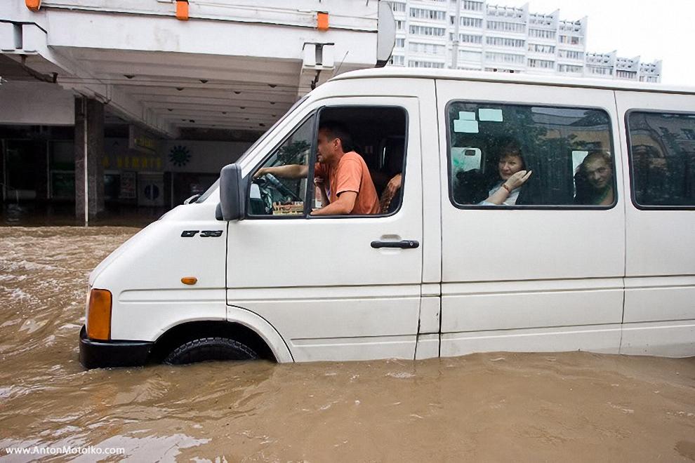 26) Спасатели подтянули к одному из троллейбусов надувную лодку, с помощью которой и будут спасать людей.