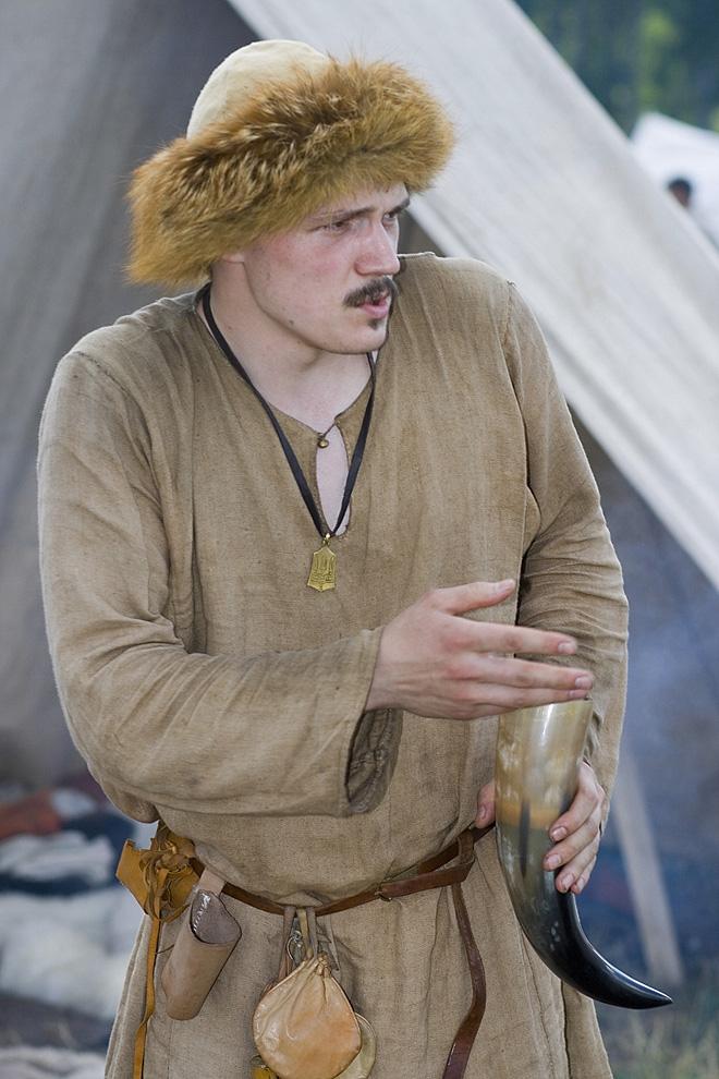 Мужчина в средневековом славянском костюме пьёт медовуху - традиционный славянский напиток- и оживлённо беседует