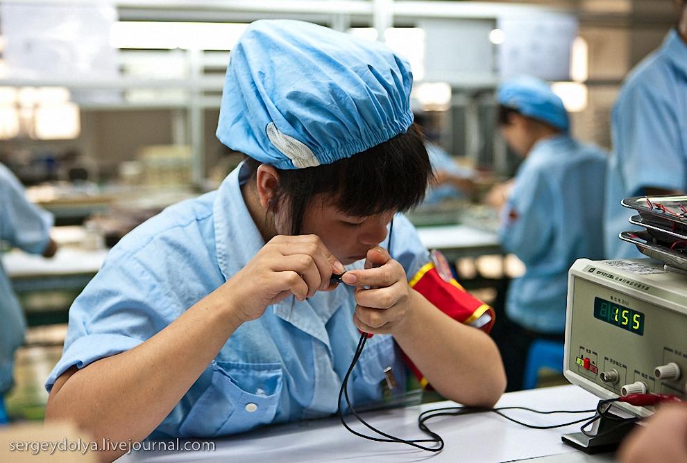 30) Работница тестирует наушники.