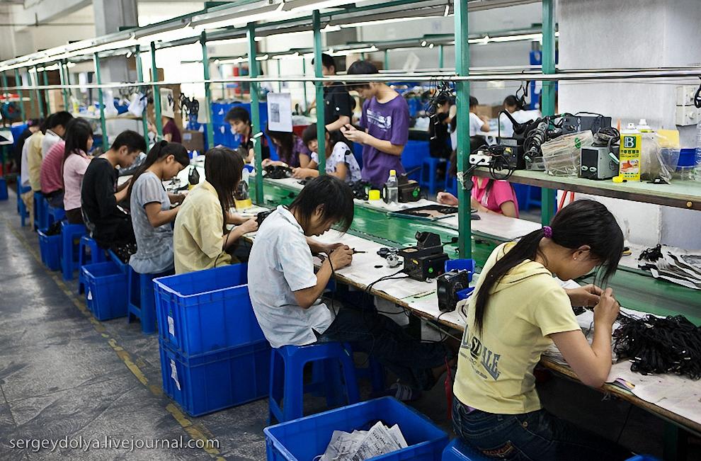 Этажом выше находится само производство. Вдоль длинного конвейера за столами сидят рабочие.
