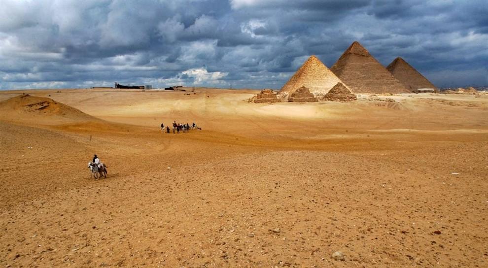 1) Туристы верхом на лошадях и верблюдах осматривают исторический памятник -  пирамиды Гизы, находящиеся недалеко от Каира. Пирамиды являются  единственным из древних семи чудес света, сохранившимся до наших дней. Кроме того, они вошли в список новых семи чудес света, составленный в 2008 году. (Muhammed Muheisen/AP)