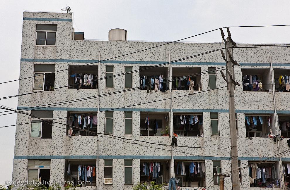 57) Все балконы завешаны сохнущей одеждой. Такое впечатление, что китайские рабочие - невероятные чистюли и ежедневно перестирывают весь свой гардероб.