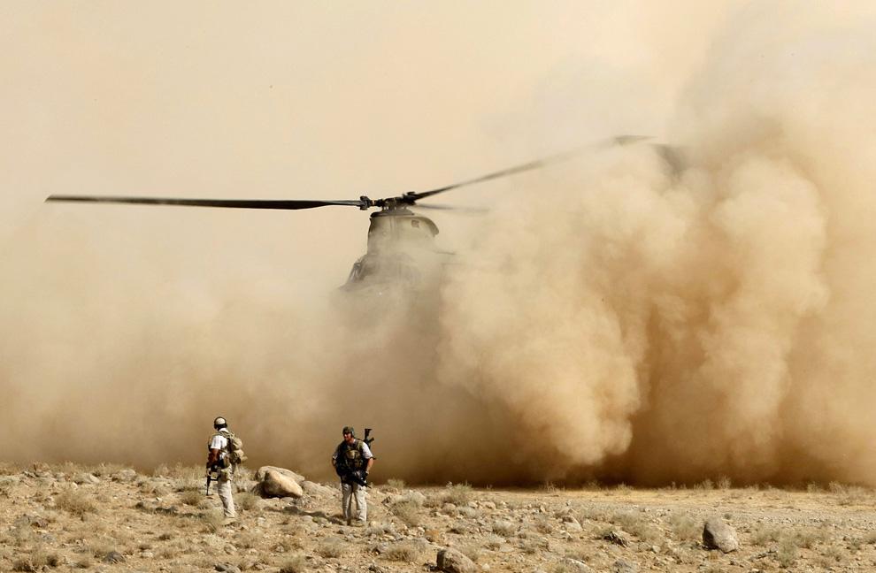 ) Люди из охраны Карла Эйкенберри, посла США в Афганистане, на фоне приземляющегося вертолета «Chinook», рядом с недавно построенным мостом на юге Тарин Кота, провинция Урузган, 9 июля 2009. (REUTERS/Tim Wimborne)