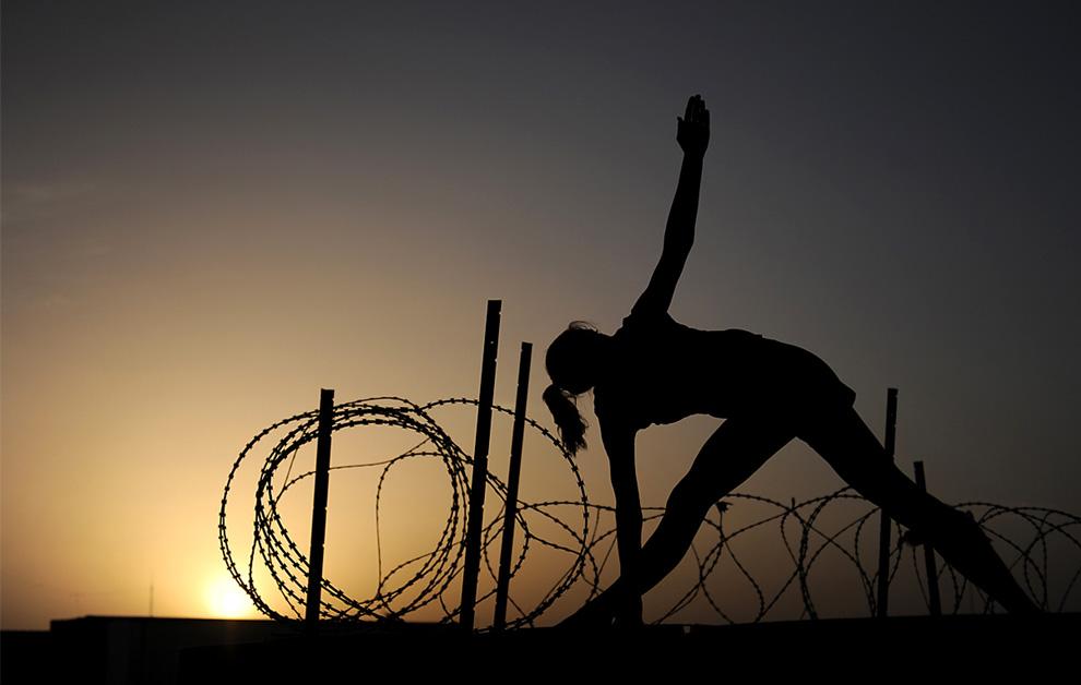 ) Младший сержант британских войск Сандра Джордан на закате делает упражнения в лагере Бастион – крупнейшей базе английских войск в афганской провинции Гильменд, 3 июня 2009. Джордан – медсестра в госпитале, где наравне со всеми военными получают медицинскую помощь и простые афганские жители. (AP Photo/Jon Bevan, Ministry of Defence)