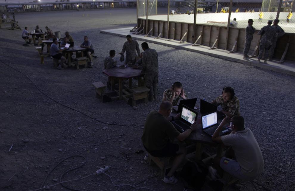 ) Румынские и американские солдаты (справа) за столом проверяют электронную почту в помещении для отдыха и развлечений, которое называется The Boardwalk на военной базе в Кандагаре, понедельник. 29 июня 2009. (AP Photo/Julie Jacobson)