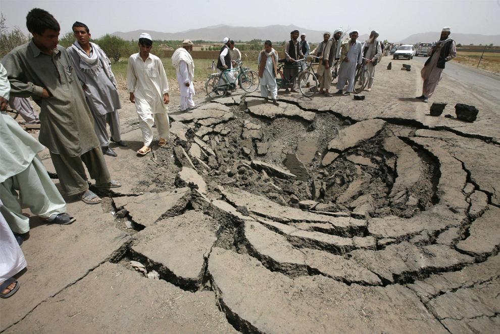 ) Афганцы столпились рядом с воронкой, оставшейся после взрыва бомбы, на главной дороге, ведущей из Кабула в провинцию Логар, четверг, 9 июля 2009. По данным полиции, в результате взрыва погибли 25 человек, в том числе 13 школьников, разрушены магазины, а обломки взорванного автомобиля раскидало в разные стороны на сотни метров. (AP Photo/Musadeq Sadeq)