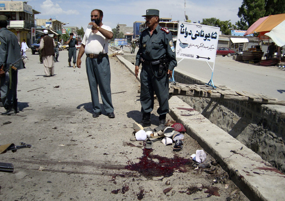 ) Афганские полицейские стоят возле пятна крови, которое осталось после взрыва террориста-смертника в городе Хосте, к востоку от Кабула, в понедельник, 22 июня 2009. Террорист-смертник на мотоцикле взорвал себя на пороге городской управы по вопросам электроэнергии, в результате чего погибли шесть мирных жителей. (AP Photo/Nishanuddin Khan)