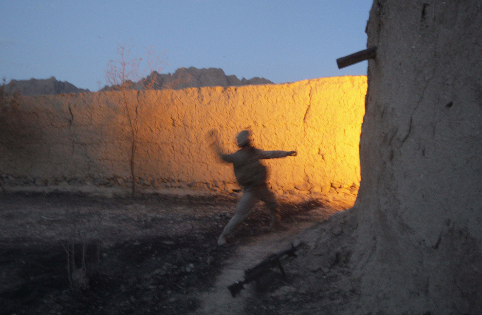 ) Американский пехотинец Дэниел Хинтер (из штата Монтана) из 2-й экспедиционной бригады МП 2-го батальона кидает гранату во время боя с талибами в округе Новзад, провинция Гильменд, суббота, 20 июня 2009. (AP Photo/David Guttenfelder)