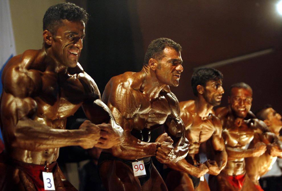 ) Афганцы позирует во время национального конкурса по бодибилдингу в кабульском кинозале 2 июня 2009. Сотни конкурсантов приняли участие в ежегодном конкурсе, организованном афганской национальной олимпийской организацией. Участники боролись за звание Мистер Афганистан. (REUTERS/Omar Sobhani)