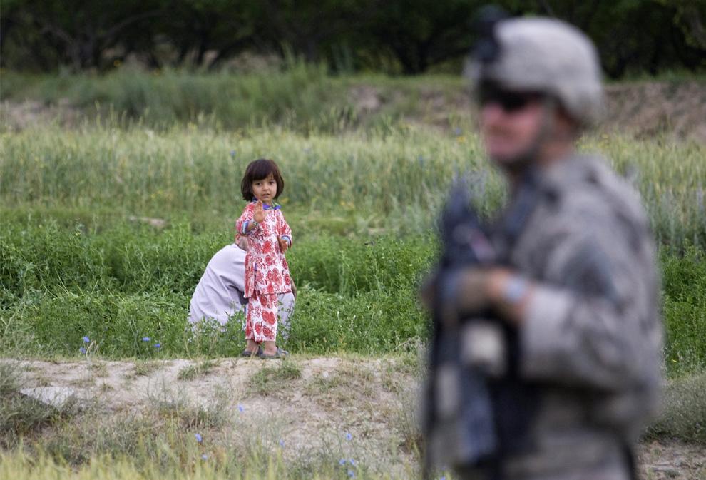 ) Девочка машет фотографу из-за спины американского солдата из 2 взвода 3-й бригады, 10-й горной дивизии, во время патрулирования деревни Молахел в горах провинции Вардак 4 июля, 2009. (REUTERS/Shamil Zhumatov)