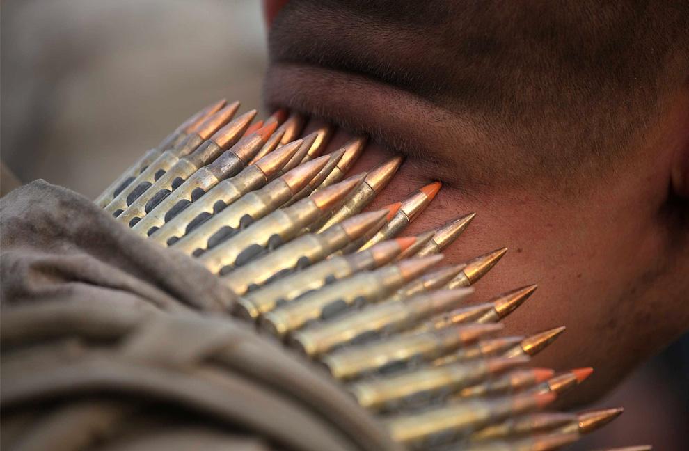 ) Американский морпех из 2-й морской экспедиционной бригады стоит с поясом из пулеметных лент на шее 6 июля 2009 года в Миан Поштех, Афганистан. (Joe Raedle / Getty Images)