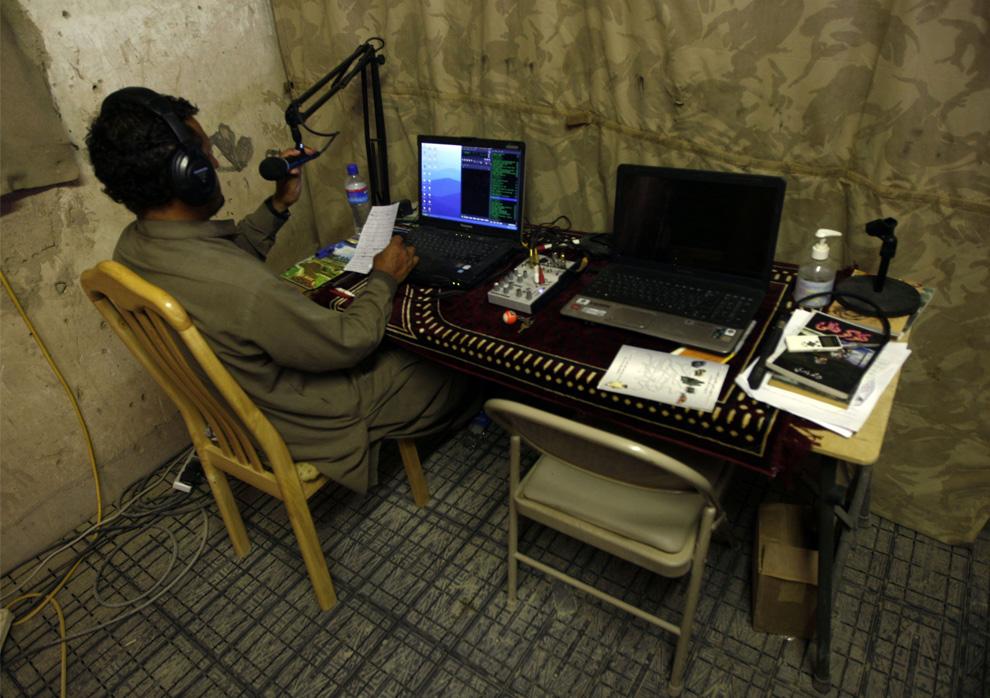 ) DJ Ashiqullah за работой на радиостанции «Garmsir» в афганской провинции Гильменд, 7 июля 2009. Стало понятно, что радио Garmsir популярно и многозначительно, когда на радиостанцию стали поступать письма. Сначала несколько, потом больше, а очень скоро слушатели стали приносить и опускать в ящик на базе НАТО, где и располагается радио в маленьком бункере,  по 20-30 писем в день. Из этих писем стало ясно, что больше всего люди хотят слушать музыку, которую талибы считали противоестественной для ислама и запрещали ее. (REUTERS/Ahmad Masood)