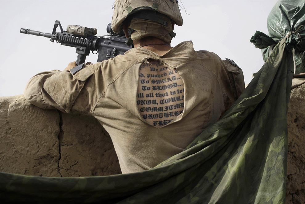 )Татуировка морпеха США из 2-й экспедиционной бригады МП 1-го батальона, видна через прореху в рубашке униформы, во время того, как он стоит на посту в полевом лагере, расположенном в районе Нава, в афганской провинции Гильменд, в среду, 8 июля 2009 год. (AP Photo/David Guttenfelder)