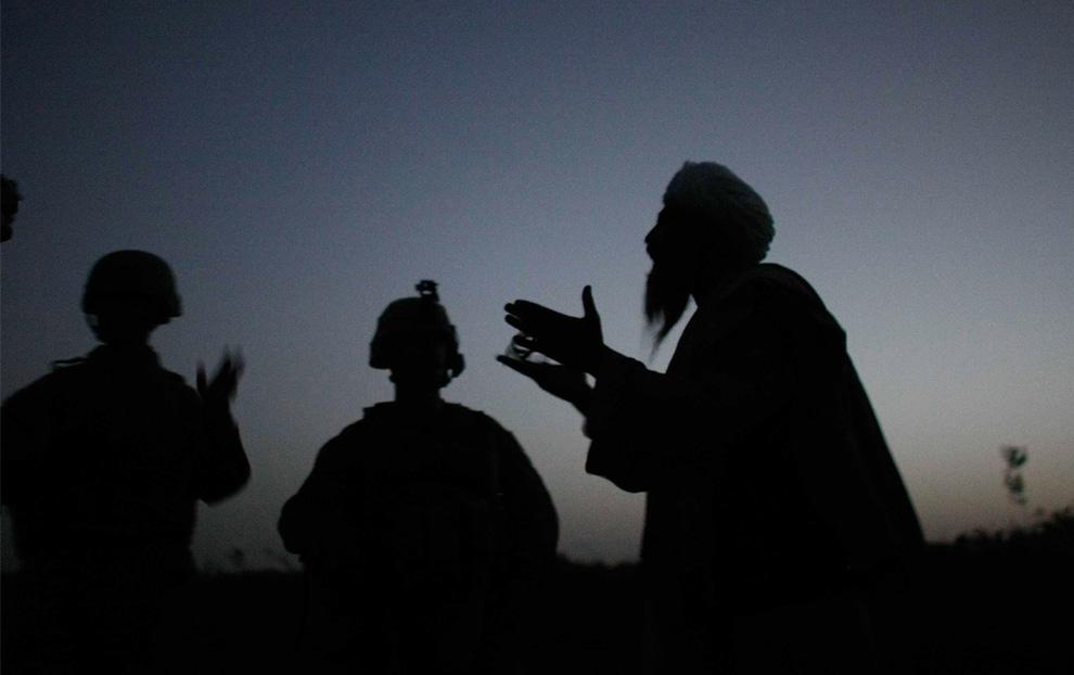 ) Американский пехотинец из 2-й экспедиционной бригады МП 2-го батальона сержант Натан Харрис (из штата Северная Каролина) (в центре) разговаривает через переводчика (слева) с афганским мужчиной после того, как было замечено подозрительное движение у базы 14 июля 2009, Mian Poshteh, Афганистан. (Joe Raedle/Getty Images)