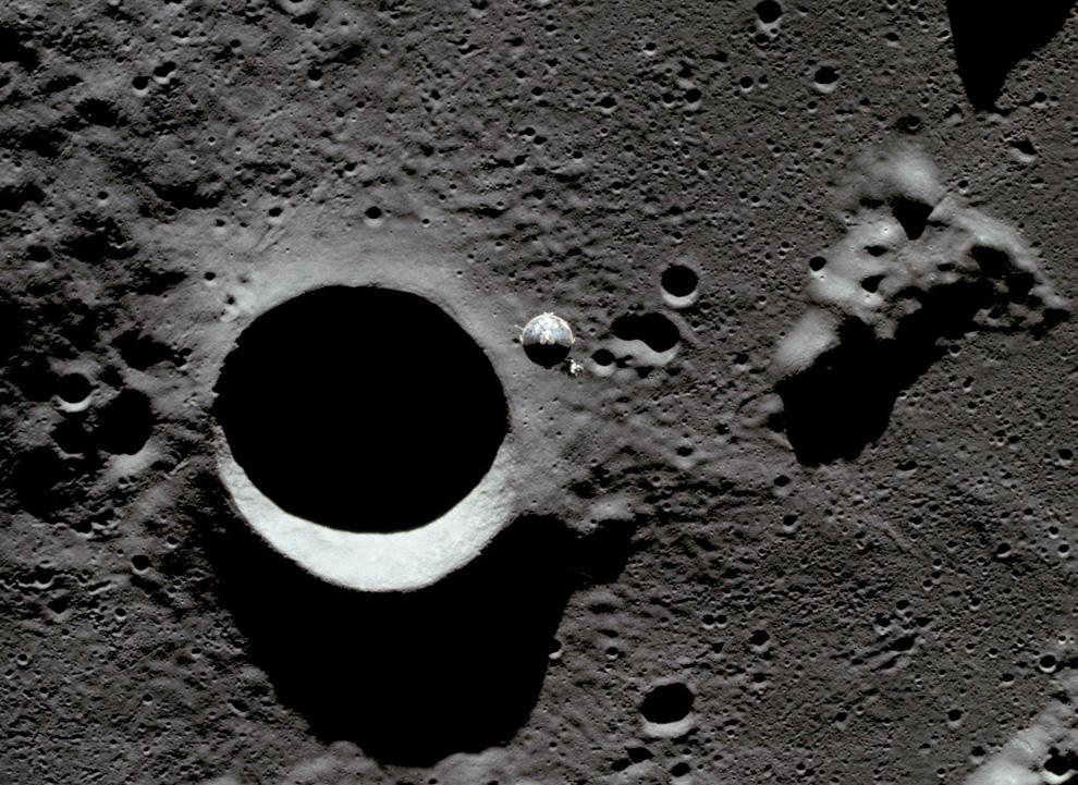 20) Вид сверху на командный и обслуживающий модули на фоне лунной поверхности из отделяющегося лунного модуля. Это последняя фотография сделанная с лунного модуля, перед началом прилунения. (NASA)