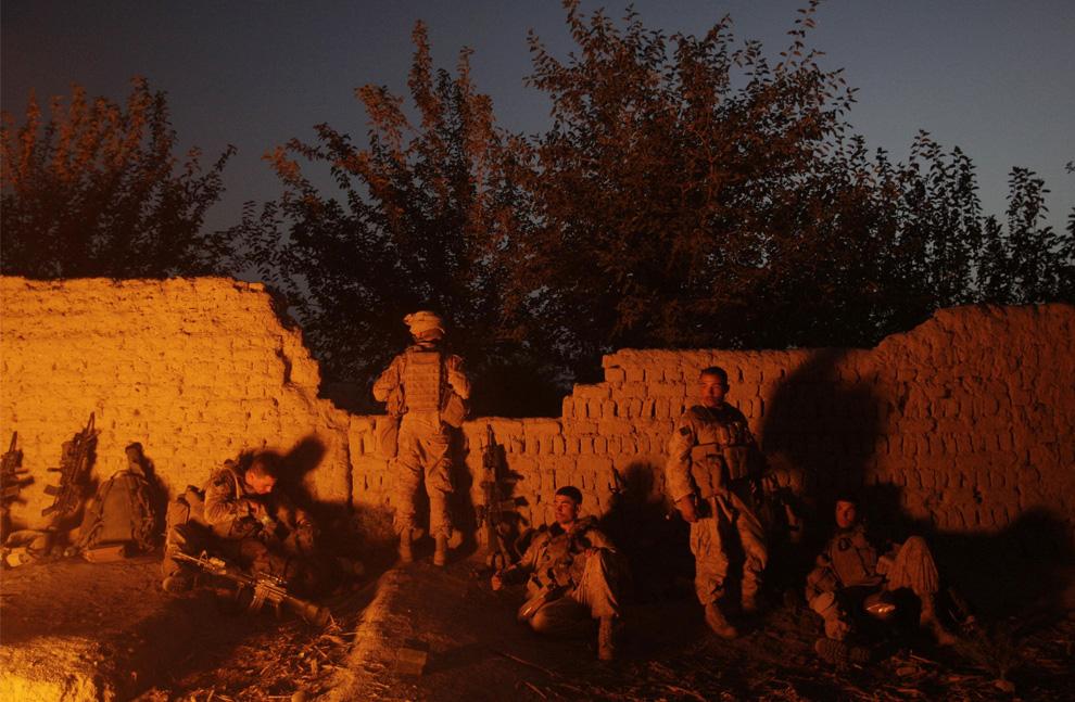 ) Американские пехотинцы из 2-й экспедиционной бригады МП, 1-го батальона у костра, в котором они сжигают свой мусор, так как им придется остаться на ночь на заброшенной ферме в районе Нава афганской провинции Гильменд, суббота, 5 июля 2009. (AP Photo/David Guttenfelder)