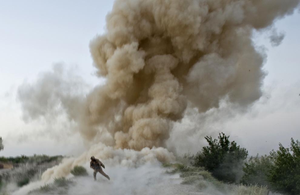 ) Американский пехотинец 2-й экспедиционной бригадой МП пытается укрыться от взрыва в районе Гармсир афганской провинции Гильменд 13 июля 2009. 2 солдата, пытавшиеся очистить путь в тыл талибов на юге провинции Гильменд погибли в результате взрыва. (MANPREET ROMANA/AFP/Getty Images)