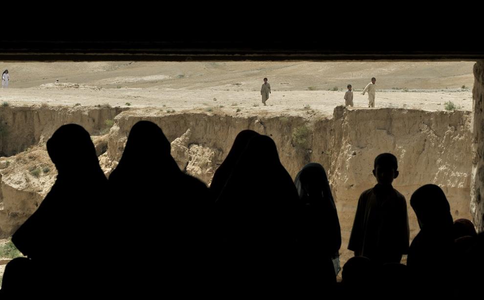 ) Пуштунские женщины и дети собрались все вместе у деревни Кафта Хана, провинция Банглан на севере Афганистана, четверг, 9 июля 2009. Сотни пуштунов были вытеснены местными таджиками и покинули свои деревни в афганской провинции Baghlan. (AP Photo/Bela Szandelszky)
