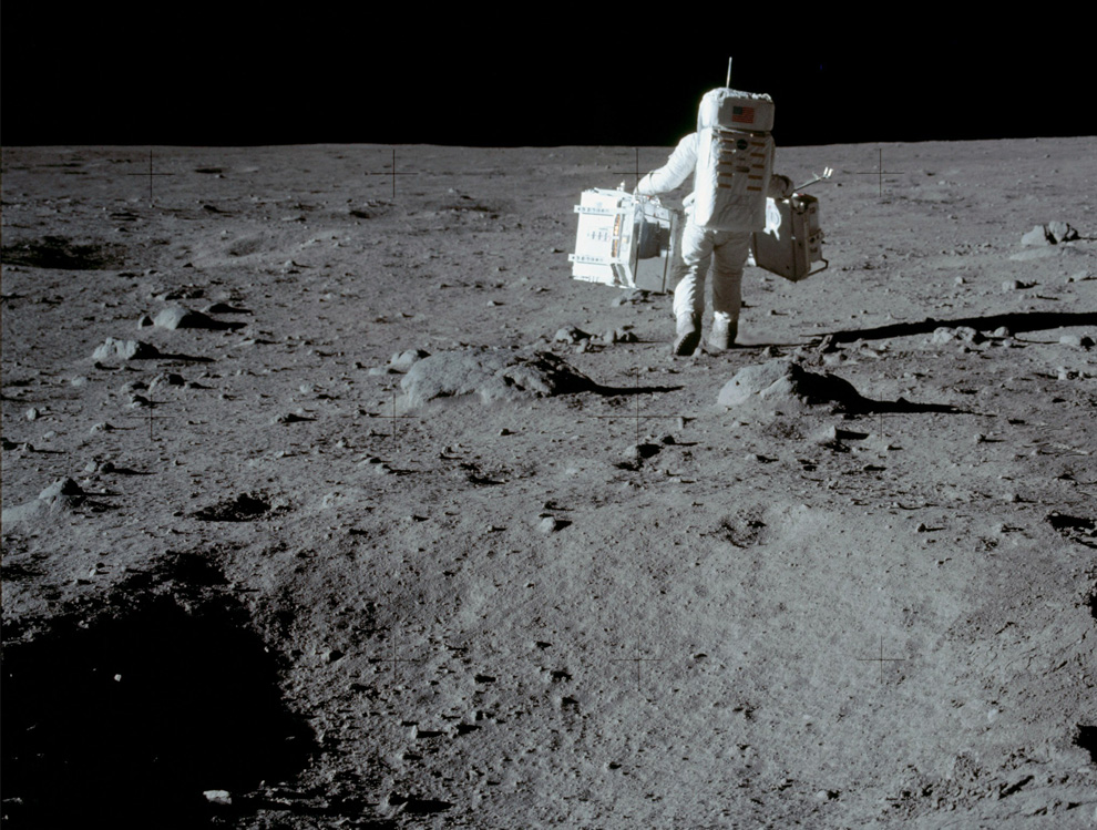 26) В во время нахождения на поверхности Луны астронавты провели несколько экспериментов. На этой фотографии Баз Олдрин несет сейсмометр. (NASA)