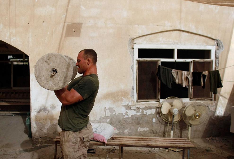 ) Младший капрал американских пехотинцев Эдисон Чиполетти (из штата Флорида) из 2-й экспедиционной бригадой МП 2-го батальона тренируется при помощи самодельных тренажеров 11 июля 2009, Mian Poshteh, Афганистан. (Joe Raedle/Getty Images)