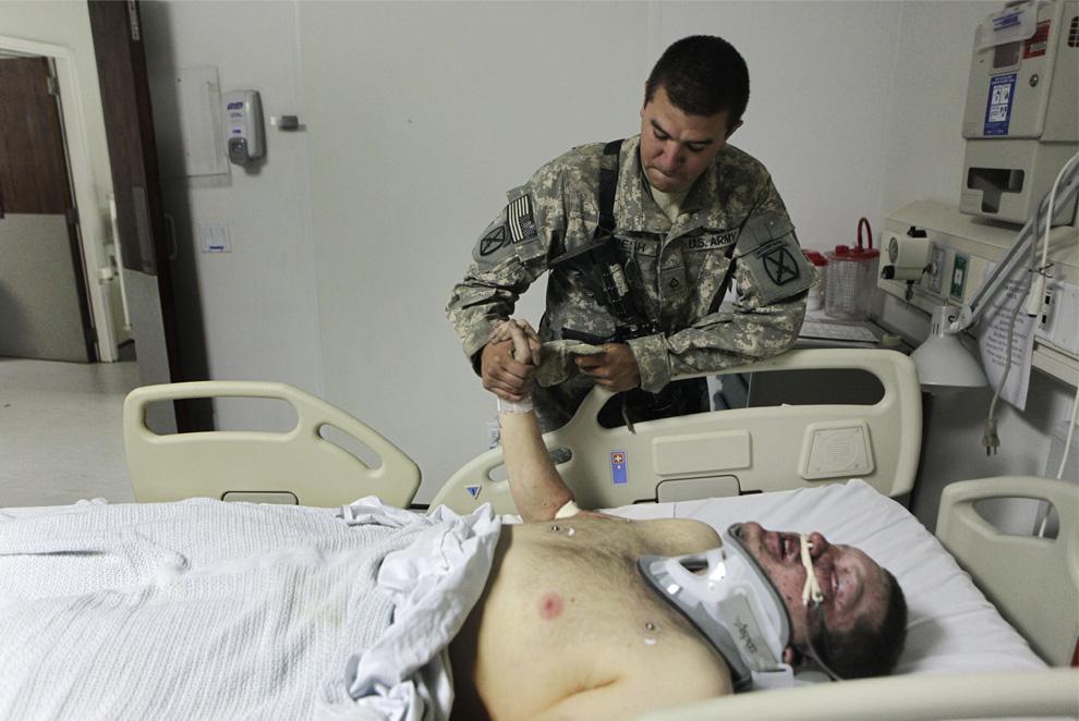 ) На этой фотографии, сделанной 1 июня 2009 года, один из пехотинцев держит руку товарища Энтони Вандергрифта (Гавайи) и сообщает ему имена 3-х человек, которые были убиты во время боя, в котором и был ранен Энтони. Снимок сделан в госпитале на базе ВВС в Баграме на севере Кабула. Вандерггрифт был ранен, а 3-е его товарищей погибли, после того как их машина подорвалась на мине в районе Неркх провинции Вардак. (AP Photo/Rafiq Maqbool)