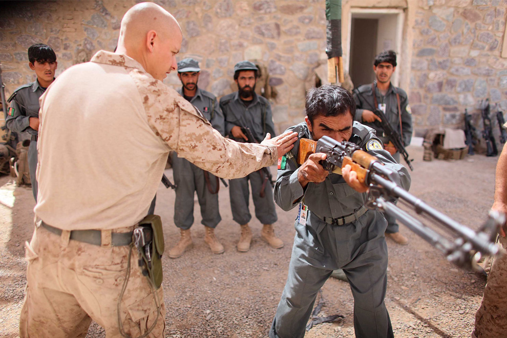 ) Сержант американской пехоты Джереми Джонсон (из штата Миннесота) из 2-й экспедиционной бригадой МП 2-го батальона показывает новичкам афганской полиции правильное положение во время стрельбы. Снимок сделан 27 июня 2009 в афганском городе Делерам. (Joe Raedle/Getty Images)