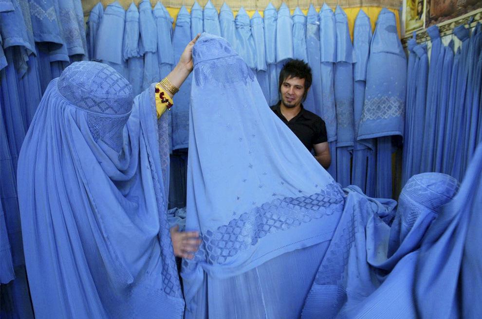 ) Афганские женщины рассматривают товар в магазине в Херате, на западе Афганистана 2 июля 2009. Продавец магазина Негматулла Юсефи (на фото не виден) рассказывает, что с 2001 года, когда талибы были изгнаны, прибыль в магазине увеличилась на 50%, кроме того, скоро ему придется устраивать распродажу абсолютно отличной от традиционной исламской одежды, чтобы еще увеличить прибыль. Фотография была сделана 2 июля 2009. (REUTERS/ Mohammad Shoiab)