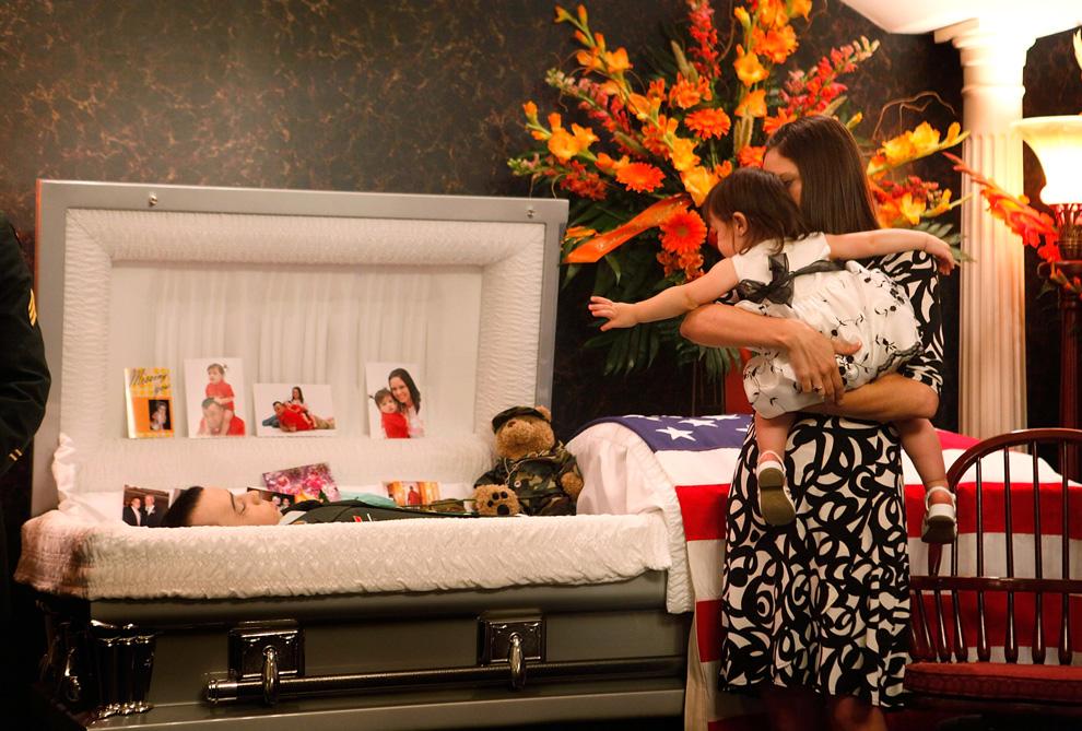 ) 16-ти месячная Обри Мелтон на руках своей матери Ларисы тянется к телу своего отца – Джоша Мелтона перед началом панихиды 27 июня 2009 года в Германтауне, штат Иллинойс. Штаб-сержант Мелтон служил в Афганистане и погиб в Кандагаре в результате взрыва бомбы 19 июня. (Scott Olson/Getty Images)