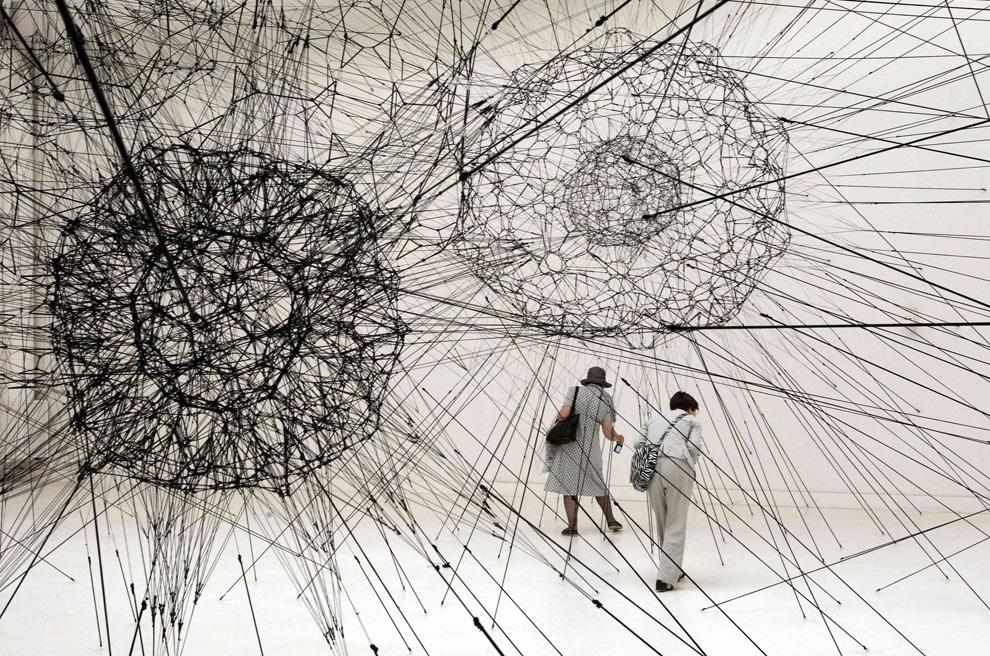 """Посетители осматривают инсталляцию под названием """"Galaxies Forming along Filaments, Like Droplets along the Strands of a Spider's Web"""" («Галактики, сформированные вдоль нитей, подобно капелькам по краям паутины паука»)  аргентинского художника Томаса Сарацено в Palazzo delle Esposizioni на вернисаже международной художественной выставки  53-ей Венецианской биеннале, 5 июня 2009. (REUTERS/Alessandro Bianchi)"""