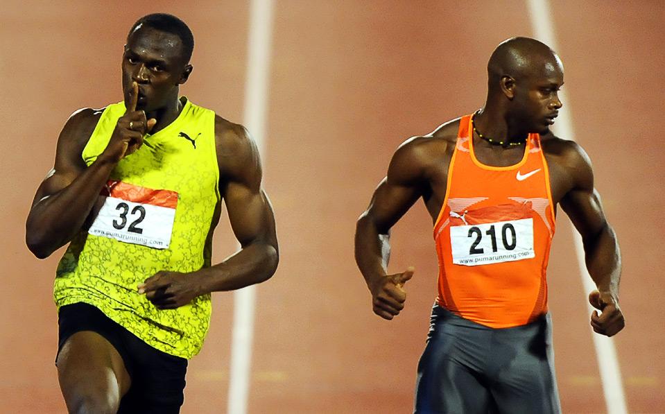 23) Усейн Болт (слева) стал победителем в беге на дистанции 100м. на Национальном Чемпионате в Кингстоне, 27 июня, 2009. (JEWEL SAMAD/AFP/Getty Images)