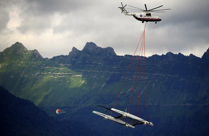 16) Огромный катамаран команды Alinghi перевозится по воздуху к подножию швейцарских Альп 8 июля. Швейцарцы перебрасывают свой катамаран на озеро Женева для дуэли с американскими конкурентами из команды Oracle. За 30 минут катамаран длиной в 90 футов был поднят российским транспортным вертолетом МИ-26 с катеростроительного завода в Villeneuve (Швейцария) и спущен на воду в порту озера Женева. (FABRICE COFFRINI/AFP/Getty Images)