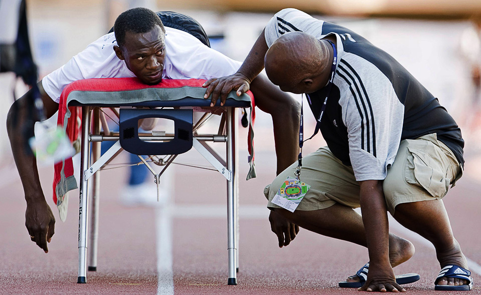 10) Олимпийский чемпион и мировой рекордсмен ямайский бегун Усейн Болт (слева) разговаривает со своим тренером Гленом Милзом во время тренировки на стадионе «Stade de la Pontaise» в Лозанне, 6 июля. (REUTERS/Valentin Flauraud)