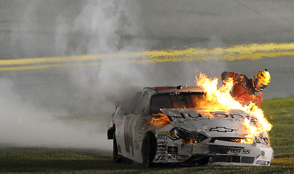 28) Кертус Дэвис выбирается из своего горящего автомобиля на гонках серии NASCAR, в которые прошли на скоростной магистрали в Дайтона-бич 3 июля. (John Harrelson/Getty Images for NASCAR)