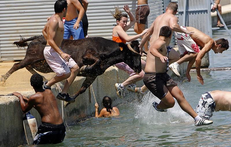 """25) Прыжки в воду во время фестиваля 'Bous a la mar' или """"Быки в море"""" в испанском городе Дения 6 июля. Позже быки доставляются на сушу при помощи лодок. (AP Photo/Alberto Saiz)"""