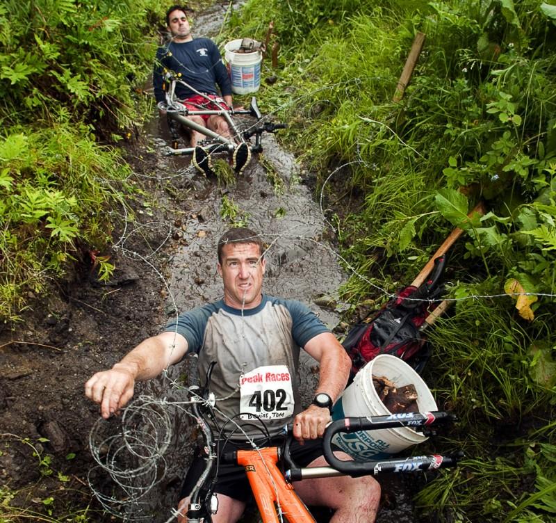 26) Том Бевинс проползает под колючей проволокой во время гонки на выживание PEAK в Питтсфилде, штат Вермонт. (Caleb Kenna for The New York Times)