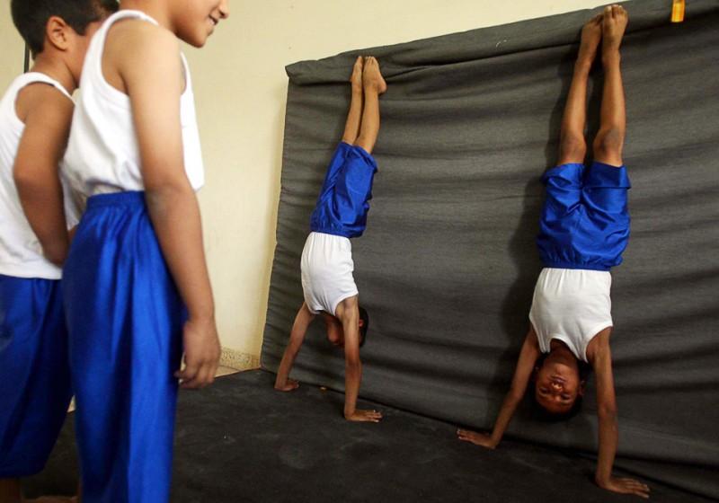 27) Иракские дети отрабатывают стойку на руках в гимнастическом зале на окраине иракского города Карбалы 12 июля. (MOHAMMED SAWAF/AFP/Getty Images)