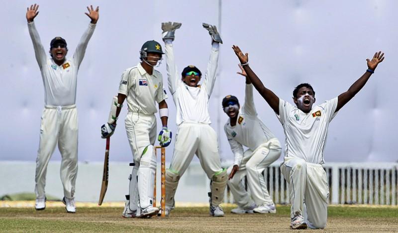 32) Аджанта Мендис (Шри-Ланка) (справа) кажется не сочувствует проигрышу пакистанца Абдулу Рауфу во время первого отборочного матча по крикету в Галле, Шри-Ланка 7 июля, (AP Photo/Gurinder Osan)