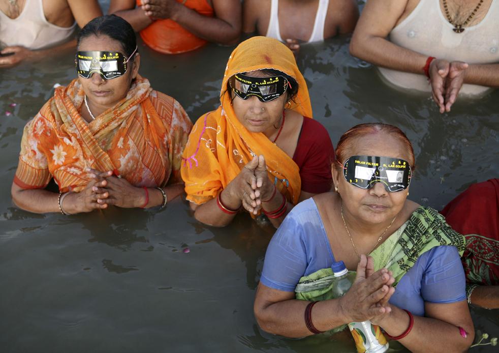 22) Индусы наблюдают солнечное затмение через специальные очки, стоя в водах Сангам, места слияния рек Ганга, Ямуна и мифической реки Сарасвати в Аллахабаде, в среду, 22 июля. (AP/Rajesh Kumar Singh)