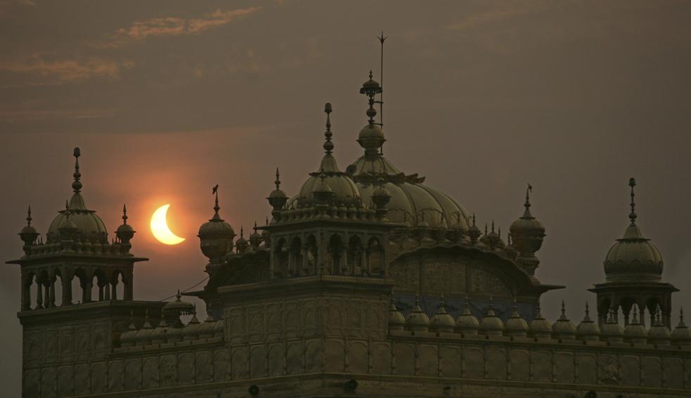 21) Частичное солнечное затмение видно над Золотым храмом, святыней сикхов в индийском городе Амритсар, в среду, 22 июля. (AP/Altaf Qadri)