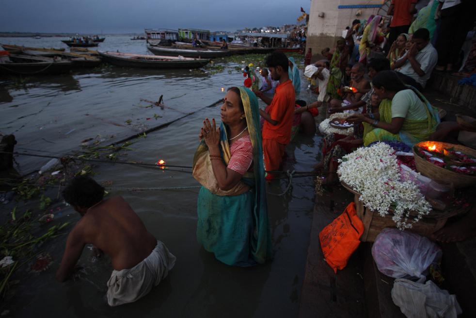 19) Индусы молятся перед началом солнечного затмения, стоя в водах священной реки Ганг в Варанаси, в среду, 22 июля. (AP/Saurabh Das )