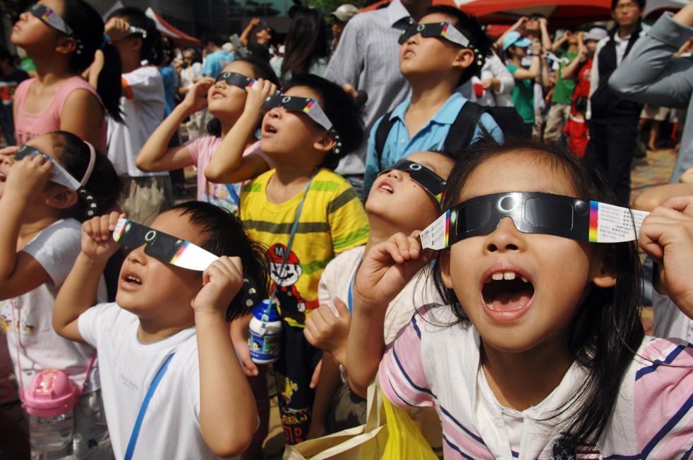 16) Дети наблюдают за солнечным затмением через защитные очки у планетария в Тайбэе 22 июля. Тайваньцы собрались в планетариях и парках, чтобы понаблюдать за самым длинным солнечным затмением 21-го века. (AFP/Getty Images/Patrick Lin)