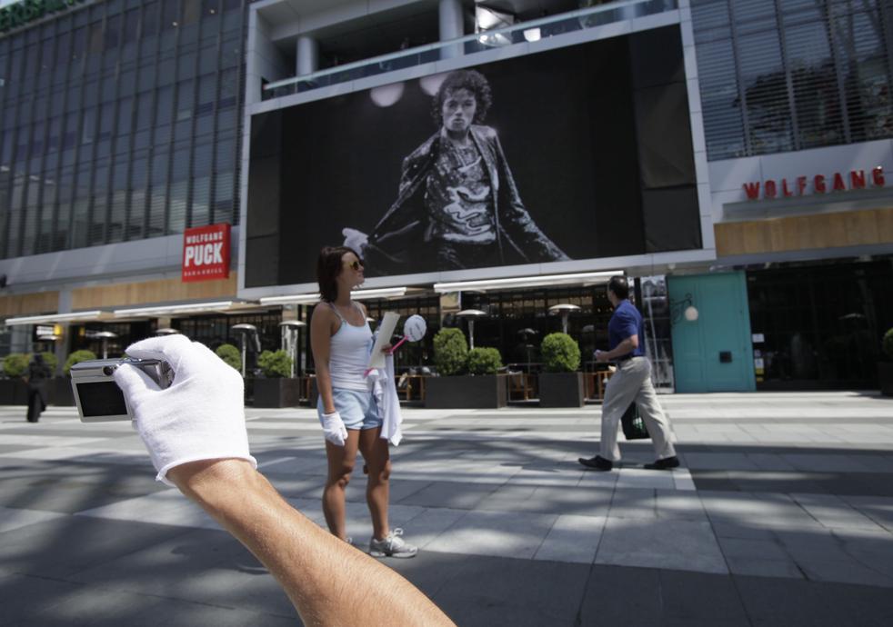 2) Фанат в легендарной белой перчатке держит фотографию Майкла Джексона у Staples Center во вторник, 7 июля, в Лос-Анджелесе. (AP/Jae C. Hong)