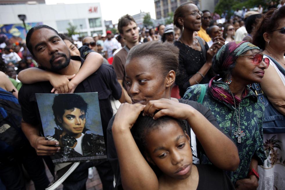 3) Ким Эшли, в центре, со своим сыном Коре Эшли на улице во время просмотра мемориальной службы Майкла Джексона в Гарлеме во вторник, 7 июля. (AP/Seth Wenig)