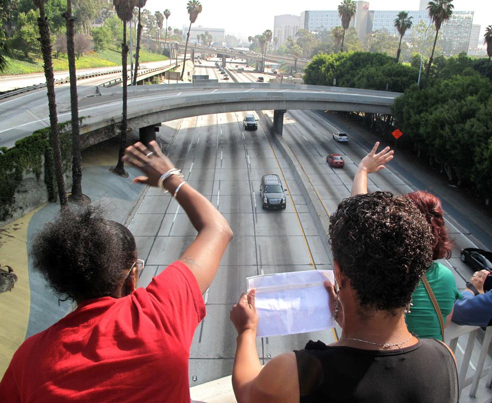 6) 43-летняя Лесли Янг, слева, и 50-летняя Мария Квейтс стоят на пешеходном мосту через 5-ю улицу, в то время как внизу проезжает похоронная процессия Майкла Джексона по пустой автостраде 110 в Лос-Анджелесе во вторник, 7 июля. Женщины вышли из своего офиса, чтобы взглянуть на то, как автомобили направляются к Staples Center на мемориальную службу Майкла Джексона. (AP/Stephanie Mullen)