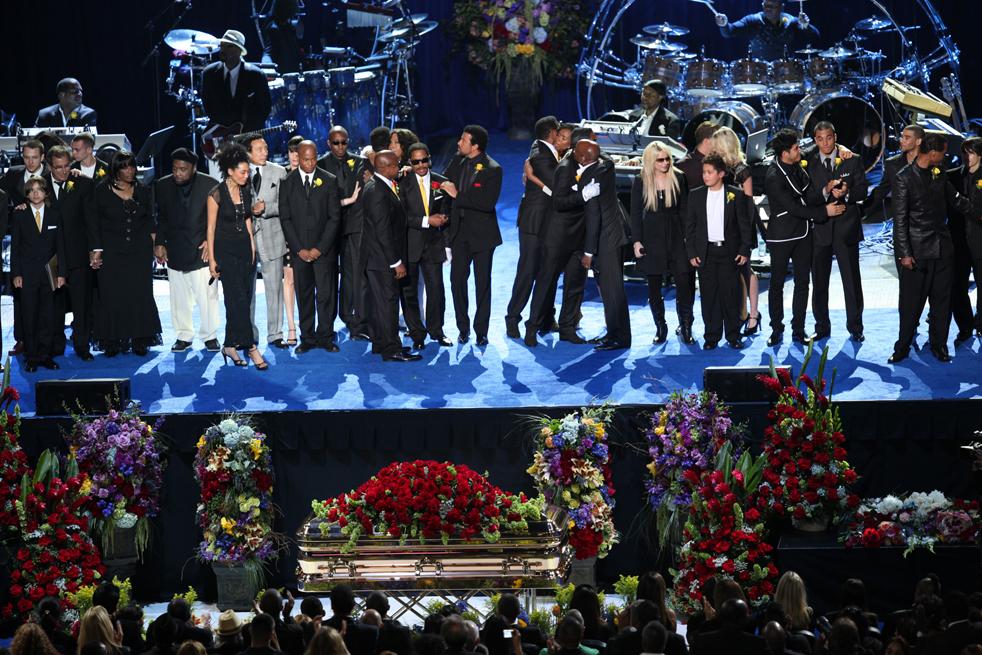 18) Члены семьи и друзья обнимаются в конце мемориальной службы в Staples Center. (AP/Monica Almeida)